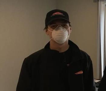 Male employee with black hat and sweatshirt and wearing a mask who is standing with a tan wall in background